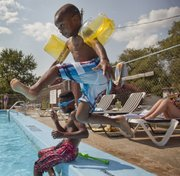 Andrew Spates, 6, jumps into the County Fair Swim Club and past his brother Andrel, 11, Tuesday, July 2. The neighborhood pool got some financial support this year from money raised by the 2013 St. Patrick's Day Parade. The pool is located at Maple Lane and Clare Road.