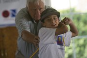 Jeff Burey, proprietor of Twin Oaks Golf Course, helps fourth-grader Javier Romero with his golf swing recently.
