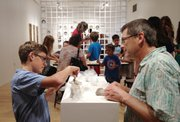Eli Jost, 15, at left, and father Jerry Jost of Lawrence mold balls of clay into sculptures during Friday's opening reception of a solo exhibit by Monika Laskowska, the Lawrence Arts Center's 2012-2013 ceramics artist in residence.