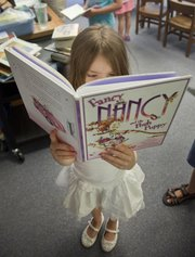 Athena Bowlin, a second-grader, is absorbed in a book she just checked out during a summer library program time at the Boys and Girls Club of Lawrence at Kennedy Elementary school.