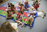 "Amy Hangen, lower right, reads from the book ""Wayside School is Falling Down"" during a summer library program time at the Boys and Girls Club of Lawrence at Kennedy Elementary school. The library is open 20 hours a week this summer and is staffed by Hangen, an AmeriCorps member."