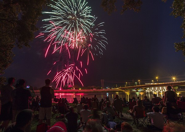 Spectators line the south bank of the Kansas River to watch the annual fireworks display Thursday, July 4, 2013.