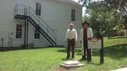 Tim Rues and Paul Bahnmeier dress in pioneer costume by the tombstone of Douglas County Sheriff Samuel Jones beside Constitution Hall in Lecompton.