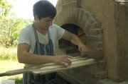 Colin Busby scores the top of a baguette before placing it inside the wood-fired oven he built at his parents' home  near Vinland.