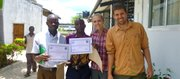 Two villagers, Golden and Selvester, stand with Peace Corps volunteers Samatha Claypool-Temple and Luke Temple after completing a training in Bagamoyo, Tanzania.