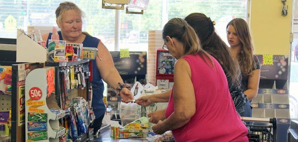 The family of Mellissa Diehl, an Osage resident and food stamp beneficiary, travels 30 miles to Topeka once each month to shop at Tilton's grocery, as well as several other area discount stores, in order to stretch their $710 monthly household income for three people — the 63-year-old Diehl (in pink) and her two adult autistic children (one of whom is pictured here). During the summer, one or both of her grandchildren (also pictured here) from her third child sometimes stay with her, too. Tilton's grocery is much cheaper than the Wal-mart in nearby Emporia, she said, because they stock past-expiration produce and other goods, damaged-packaging items, and other cheaper foodstuffs.