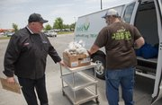 Kurt Brewer, managing partner at LongHorn Steakhouse, left, helps Just Food volunteer Richard Beebe load up surplus food, including potatoes and rib loin, from the restaurant. The Lawrence LongHorn donates food such as fresh fish, meat, soups and vegetables weekly to the food pantry through a program organized by LongHorn's parent company.