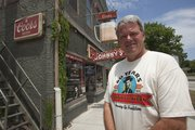 Rick Renfro, owner of Johnny's Tavern in North Lawrence, stands outside the bar and grill, which is celebrating its 60th anniversary this year. The original owner, John P. Wilson, hung the beer sign behind Renfro when he opened the bar in 1953.