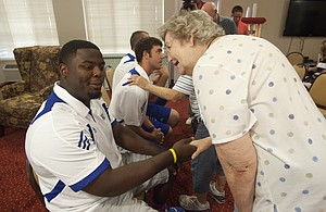 Richard Gwin/Journal World Photo.KU football player Marquel Combs, shakes hands with resident Rose Tare-Smith, as a handful of KU football players were on hand at the Meadowlark Estates Retirement Home at 4430 Bauer Farm Drive to get some first hand information on KU football