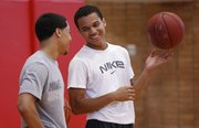 "Lawrence High senior Anthony ""Bootsy"" Riley, right, laughs with sophomore Justin Roberts during summer basketball camp on Wednesday, July 10, 2013, at Lawrence High."