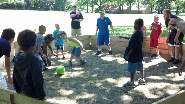 Youth and staff playing Gaga Ball in the park.