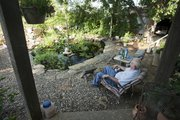 Jay Robertson, of rural Lecompton, relaxes next to one of the ponds in the backyard of his home. He and his wife, Connie, have added several ponds and waterfalls to their landscape over the years, along with flowers, shrubs and other beautiful kinds of plants.