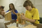 Neva Gregory, 13, left, and Abigail Meier, 13, work on bird houses on July 12, 2013,  as part of the Summer of Services youth volunteer program. Made possible with financial support from the Douglas County Community Foundation, the Summer of Service is now in its fourth year, and this year it added internships for teenagers.