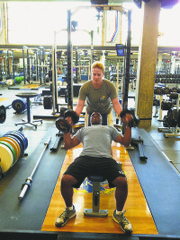 Kansas University strength-and-conditioning coach Andrea Hudy, top, works out with Sgt. Michael Pride on Wednesday during Pride's visit to the KU campus. Pride is in town to pick up pointers from Hudy for the Wounded Warriors Project, for which he is a coach.
