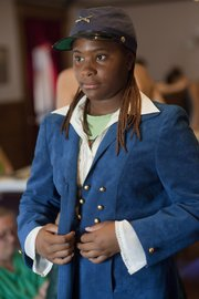 LaMisha Hollywood-Johnson, 15, shows off a military-style jacket she created at the Watkins Community Museum of History as part of the Civil War Fashion Workshops this summer.
