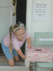 Heidi Burke, 9, checks the donation box outside her home in Shawnee on July 8. Heidi, a quadrilateral congenital amputee, used PayPal to raise almost $9,000 to help a friend from England attend a convention with her.