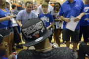 Fans gather around former Kansas basketball player Mario Chalmers for autographs during a break at the Chalmers All Pro Celebrity basketball game Thursday at Olathe East.