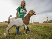 Eight-year-old Halley Flory, Baldwin City, stands with her goat, Chip, as he lets out a call after taking a short walk. Halley raised Chip to show at the Douglas County Fair.