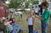 Maddy Welch, 9, a member of the Kanwaka 4-H Club, gets her hair braided into a pony tail by her mom and fair board member Kate Welch Saturday, July 27 before the 4-H Horse Show at the Douglas County Fairgrounds. Welch was competing with her horse Nick, in background, in the showmanship event. At left are Maddy's father Sean and brother Billy 10, all from Lecompton.