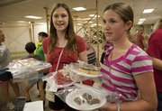 Sisters Kyleigh Leslie, left and Morgan Leslie, of the Kanwaka 4-H Club, carry their baked goods to the judges Monday at the Douglas County Fair.