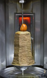 Shawarma is heated on a vertical grill inside the Lebanese Flower, 1016 Massachusetts St.