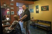 Marty Olson, owner of Do's Deluxe at 416 E. Ninth St., works on Susan Schott's hair. Olson routinely displays work by local artists in his salon, as a way to add to its decor and also to support the artists' sales and visibility.