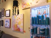 Original artwork by several area artists, including Jaime Hubert-Rovenstine's paintings in the foreground, is on display next to hair products at the Blue Dot Salon, 15 E. Seventh St. The salon is one of a number of Lawrence businesses that offers its wall space to artists trying to sell their work.