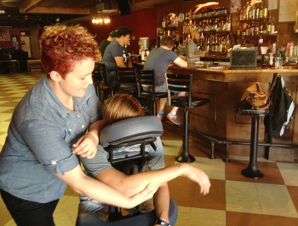 Aimee Schalles, a licensed massage therapist from Body Boutique, gives a chair massage at Jackpot Saloon.