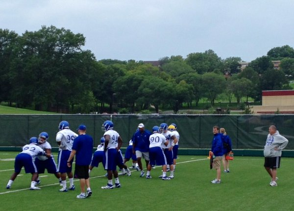 KU coach Charlie Weis (right, in gray sweatshirt) watches the D-Line go through drills during the initial fall practice of the 2013 season on Thursday.
