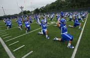 The Kansas Jayhawks stretch out on the field in rows during the first day of football practice on Thursday, Aug. 8, 2013. Nick Krug/Journal-World Photo
