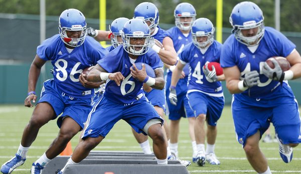 Kansas running back Darrian Miller (6) weaves through some pads as he works out with the running backs and fullbacks during the first day of football practice on Thursday, Aug. 8, 2013. Nick Krug/Journal-World Photo