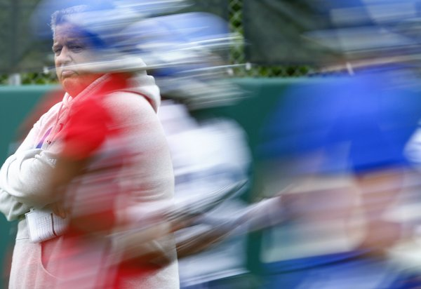 Kansas head coach Charlie Weis is seen behind a blur of players running through warmups during the first day of football practice on Thursday, Aug. 8, 2013. Nick Krug/Journal-World Photo