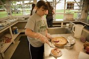 Sophie DeChant 11, of Vinland cuts a slice of cherry pie to sell at The Vinland Fair on Thursday August 8, 2013. The fair has been going strong since 1907, and the fair grounds were busy with families and their children.