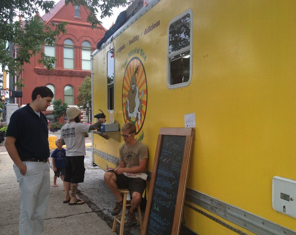 Jason Hering, one member of the co-op that owns and operates the Blissful Bite food truck, takes lunch orders Friday, Aug. 9, 2013, in the parking lot at 11th and Massachusetts streets.