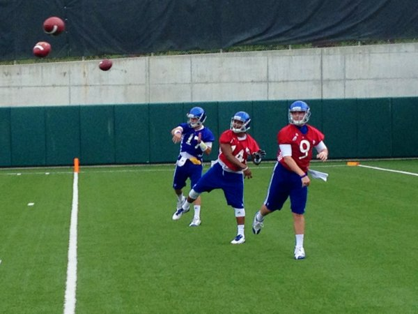 KU quarterbacks Jake Heaps (right), Michael Cummings and Blake Jablonski work throwing drills during Friday's practice.