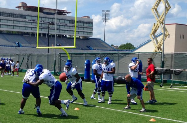 The KU defensive line works on a fumble drill during Sunday's practice, the final day the Jayhawks were forced to wear shells before moving to full pads.