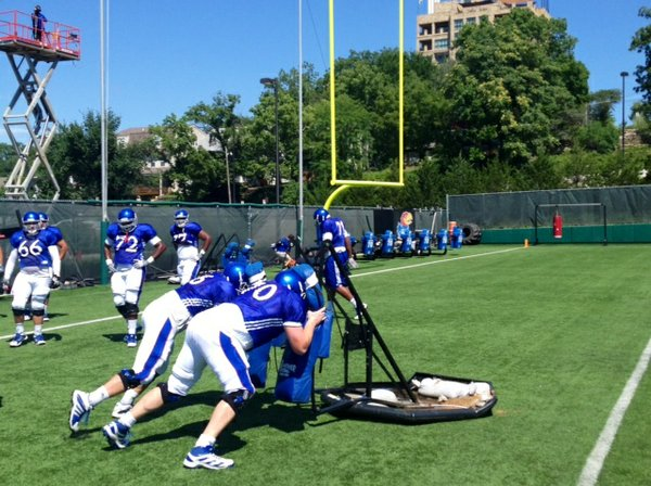 KU offensive linemen Gavin Howard (70) and Bryan Peters (76) push the sled during an O-Line warm-up drill at Monday's practice.