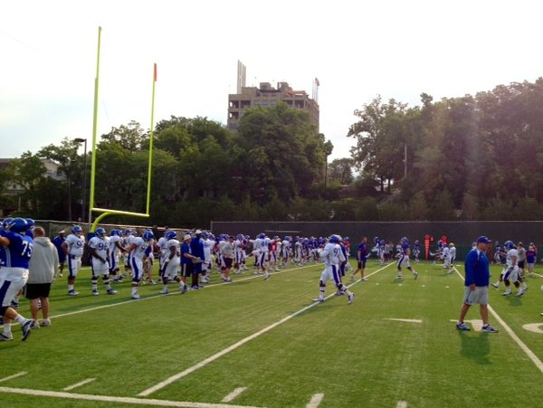 Signs of the early-morning sunshine peek over the trees at KU football practice on Tuesday.