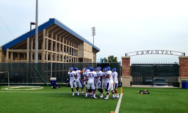 The KU defense huddles in the end zone after running through a drill designed to handle turnover transitions at Tuesday's practice.