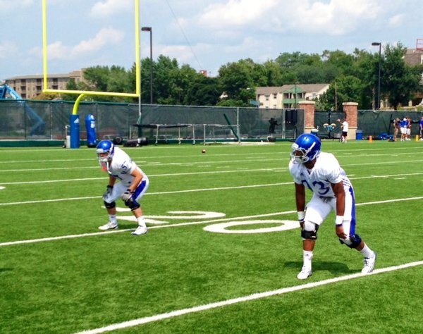 Jake Love (left) and Ben Goodman run through a footwork drill during Wednesday's KU football practice.