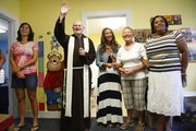 Terri Broadwell, from left, Molly Green, Pat Johnson and Edie Willhite stand with Father Mike Scully as he blesses the Saint John preschool building Thursday at Saint John Catholic School. Scully and Father Jeff Ernst toured the school, including the much-awaited addition to the main building, with an aspergil of holy water for blessing each room in preparation for the new school year, which begins Monday.