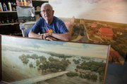 Paul Penny, 88, is pictured in his studio in the basement of his Old West Lawrence home. In front of him is a painting he did long ago of the 1951 flood, and behind him is a work in progress of the Kansas University campus. Around the 1950s, Penny painted a picture of Quantrill's raid that now hangs on the Missouri side of the state line.
