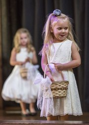 Two-year-old Avery Lakin, foreground, and her sister Kennedy, 4, both of Olathe, dress as flower girls during The Bridal Event, held Saturday at Abe & Jake's Landing in downtown Lawrence.