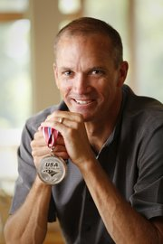 Lawrence resident Ross Freese, 50, recently placed second in his age group at the USA Triathalon in Milwaukee, qualifying him for the World Triathalon in Edmonton, Alberta next summer. Freese is pictured on Aug. 17, 2013, with his silver medal.