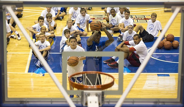 Eleven-year-old Chris Fields waits for his turn to shoot as he and former Kansas University player Ben McLemore duel it out in a game of knockout as other campers watch during the Bill Self basketball camp Saturday at Allen Fieldhouse.