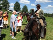 On Saturday in western Missouri, a William Quantrill re-enactor talks to attendees of a bus tour of Quantrill's raiders' path to Lawrence in August 1863.