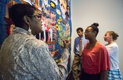 "Marla Jackson, left, discusses ""Still We Rise"" with three of the teens who helped her design and make the quilt, Alyssia Ivory, 17, Topeka, front, Tiffany Jirik, 16, Topeka, and Kenyan Bell, 15, Lawrence, Sunday when the quilt was on display during a special event at the Spencer Museum of Art."