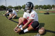 Lawrence High senior Drew Green (41) loosens up on the first day of practice on Monday, Aug. 19, 2013, at LHS.