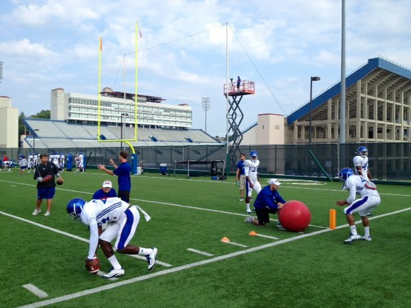 KU's defensive backs work on a fumble recovery drill with DBs coaches Scott Vestal and Dave Campo at Monday morning's practice.