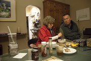 Angela Nascimento sits at her dining room table with partner Kent Smalter, who has ALS, as the pair enjoy a meal together.